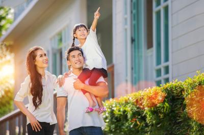Un couple avec enfant contemple une maison
