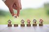 immobilier neuf bordeaux - une main plaçant de petites maisons sur des piles de pièces de monnaie