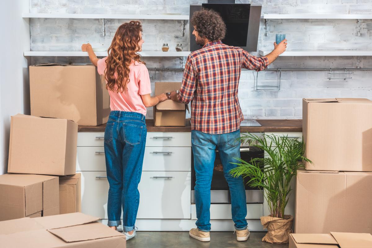 Projet immobilier à Bordeaux – Couple de dos installant ses affaires dans un logement qu'il vient d'acheter