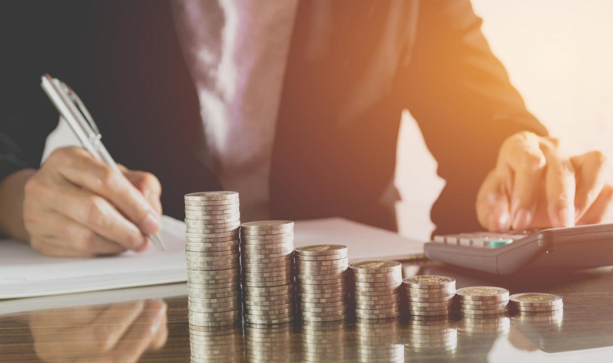 Investir à Bordeaux en 2024 - Homme calculant ses impôts devant des piles de monnaie